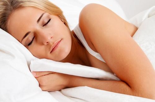 Schlafende blonde Frau in einem Bett mit weißem Bettbezug